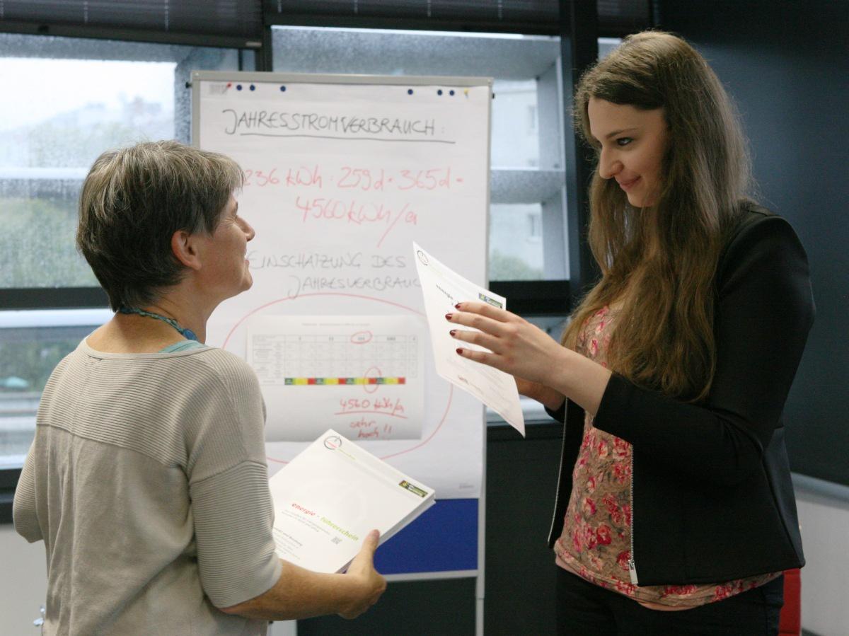 Gespräch Kursleiterin und Teilnehmerin vor Flipchart